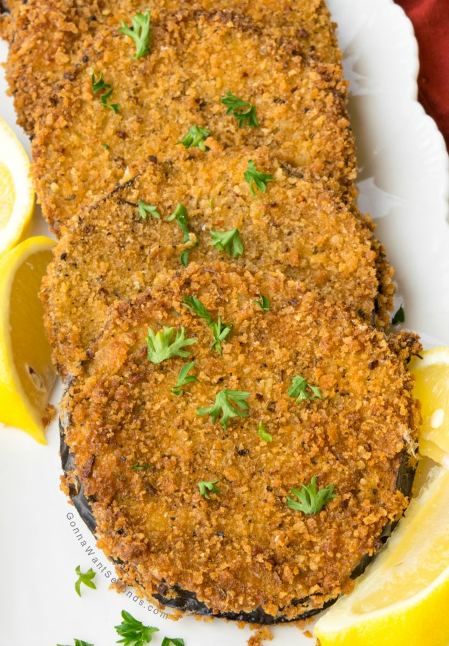 Fried Eggplant coated with panko breadcrumbs with lemon garnish on white plate