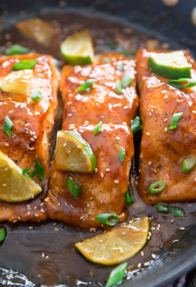Honey Glazed Salmon on a Platter Garnished with Sliced Limes, Chopped Green Onions, and Sesame Seeds