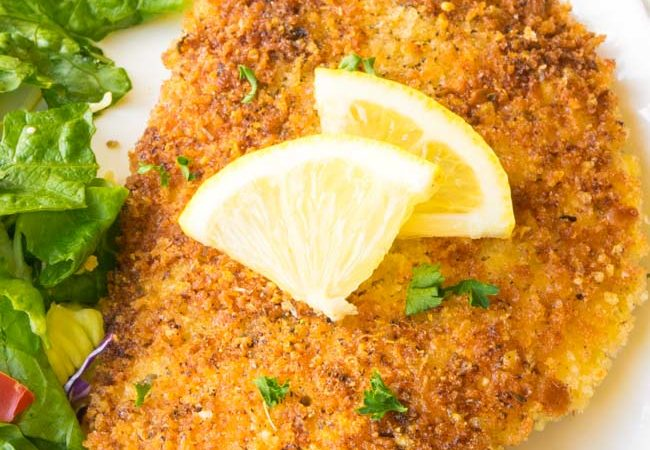 Chicken Milanese on white platter garnished with lemon with leafy greens on the side