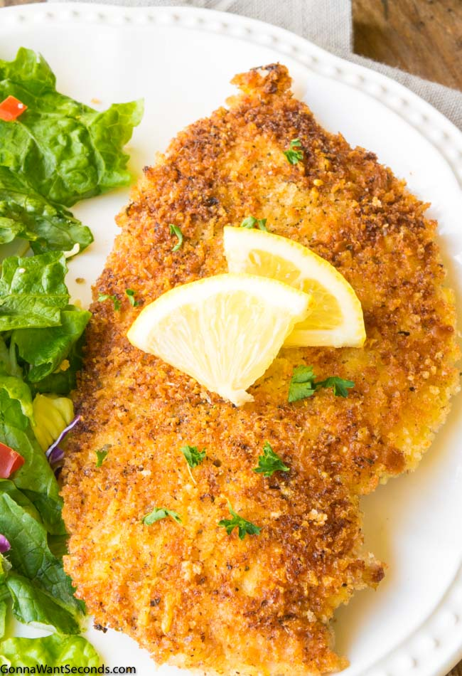 Chicken Milanese on white platter garnished with lemon with leafy greens on side