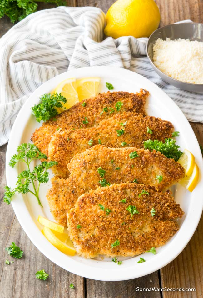 Chicken Milanese on white platter garnished with lemon and parsley