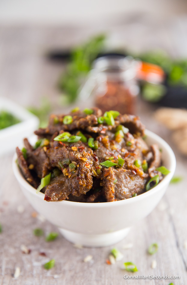 Hunan Beef sprinkled with green onions and red chili flakes in a white bowl