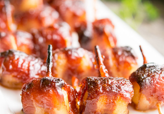 Bacon Wrapped Water Chestnuts on a White Rectangular Platter