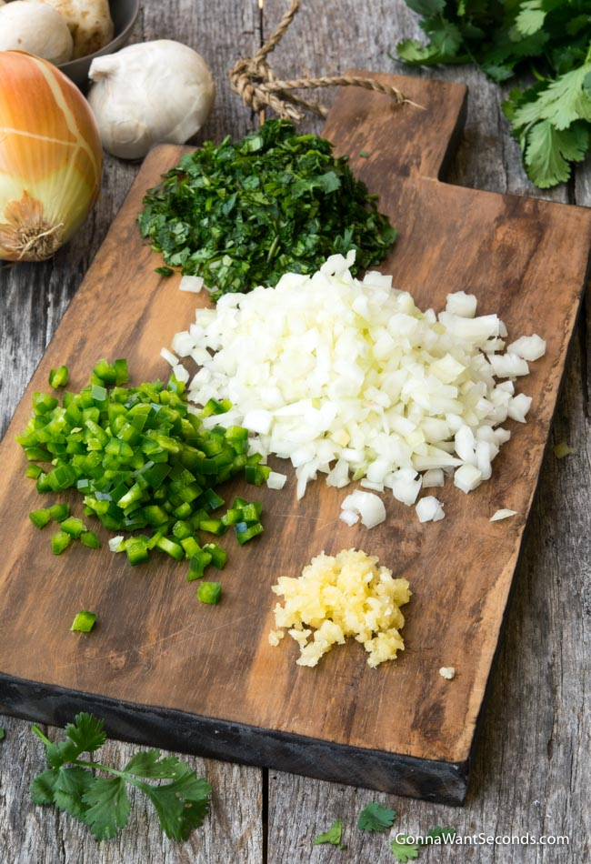 Finely chopped onions, jalapeno, garlic, and cilantro on a wooden chopping board