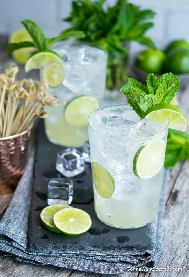 Two highball glasses filled with Lime Rickey, ice, and lime wedges