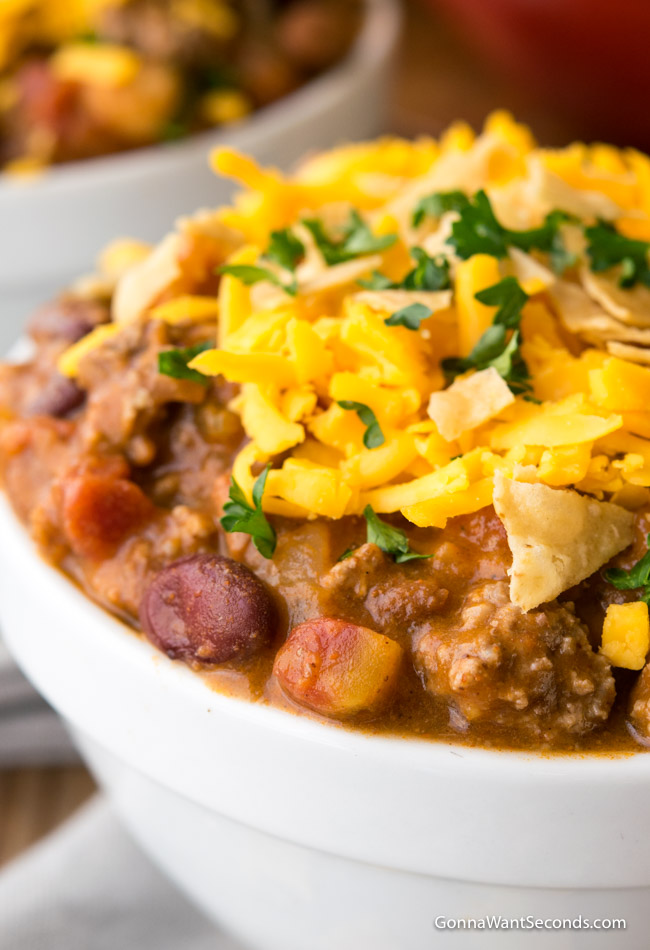 A close up shot of Taco Chili topped with shredded cheese in a white bowl