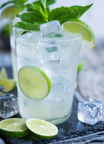 A highball glass filled with Lime Rickey, ice, and lime wedges