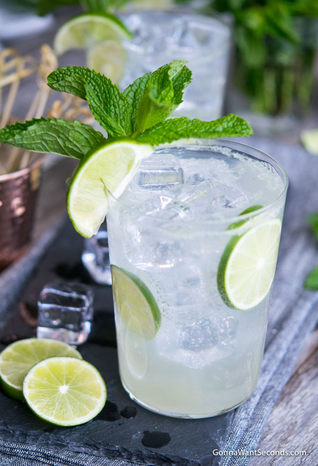 A highball glass filled with Lime Rickey, ice, and lime wedge