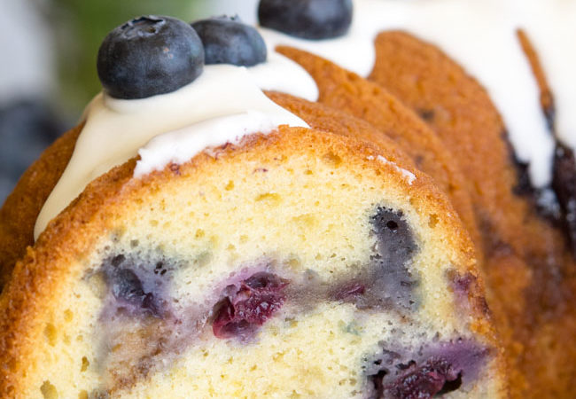 Whole Blueberry Coffee Cake with glaze and fresh blueberries on top