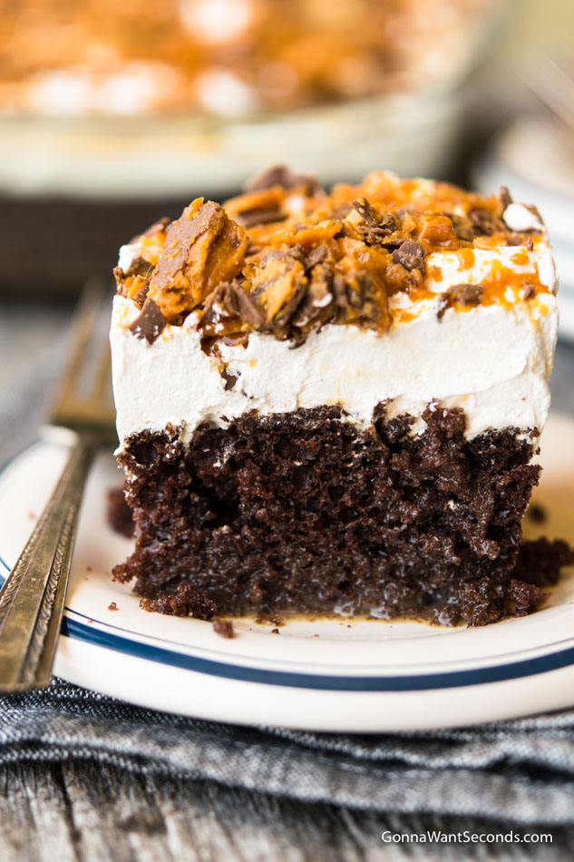 A slice Butterfinger Cake on a plate with fork on the side