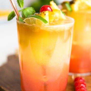 Planters Punch garnished with a skewer of pineapple wedge, thin orange slice, and a maraschino cherry. With metal straw.