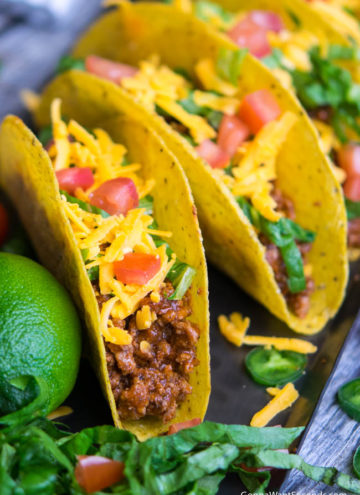 Turkey Tacos topped with shredded cheese and tomatoes in a tortilla
