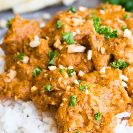 A bowl of rice topped with Butter Chicken garnished with parsley and ground cashews