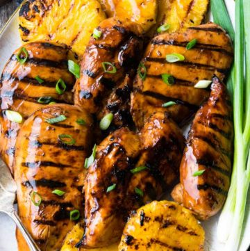 Grilled Huli Huli Chicken with grilled pineapples sprinkled with sliced green onion in a serving plate
