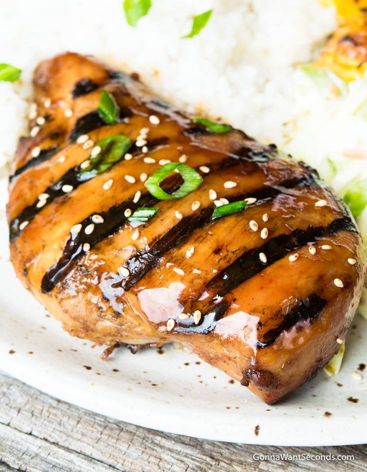Grilled Huli Huli Chicken sprinkled with sesame seeds and sliced green onion with rice on the side
