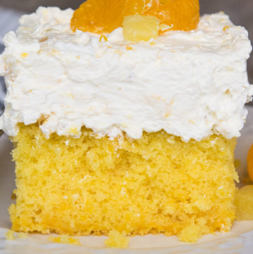 A slice of Pig Pickin Cake topped with mandarin orange and crushed pineapple on a plate