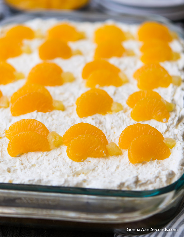 Pig Pickin Cake topped with mandarin orange and crushed pineapple in a 9x13 glass baking pan