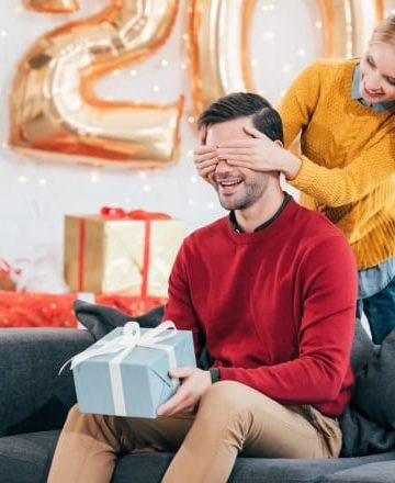 24 Best Christmas Gifts For Your Hubby man holding a gift box while a woman covers his eyes with her hands