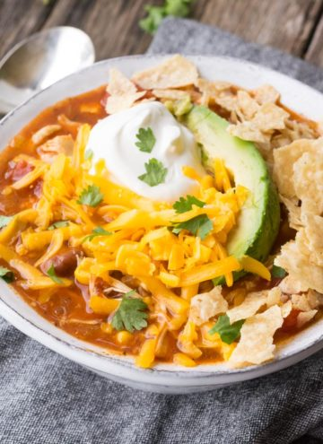 Chicken Taco Soup topped with a dollop of sour cream, cheese, and tortilla chips in a white bowl