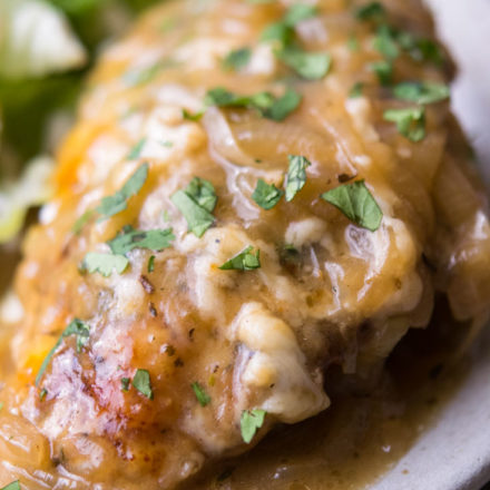 French Onion Chicken with greens on the side, on a plate