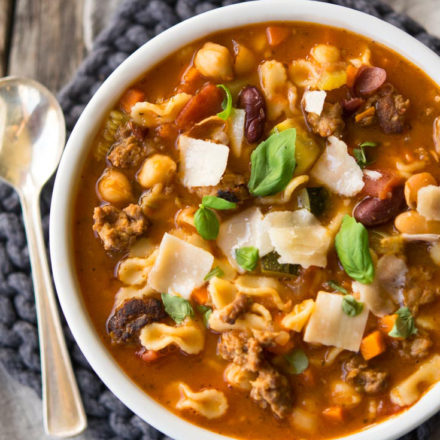 Italian Sausage Soup garnished with basil and cheese, in a bowl