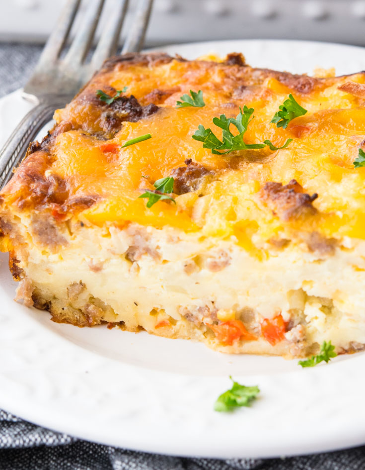 A slice of Bisquick Breakfast Casserole on a plate with fork