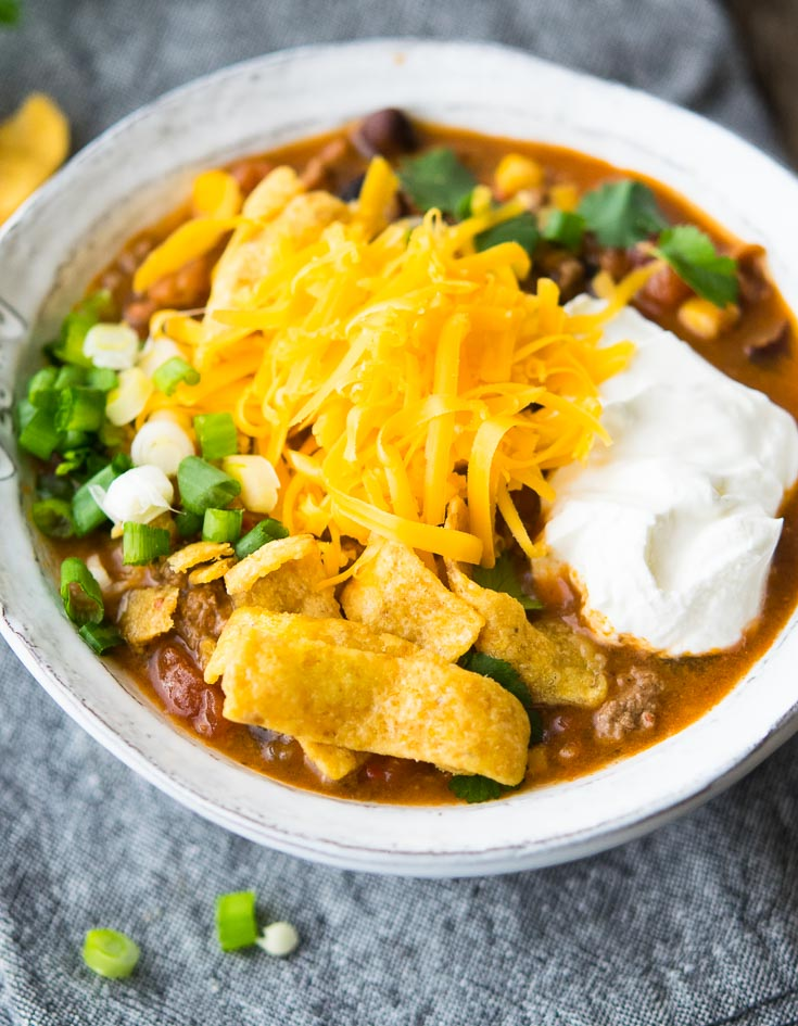 Taco Soup topped with corn chips, shredded cheese, a dollop of sour cream, in a white bowl