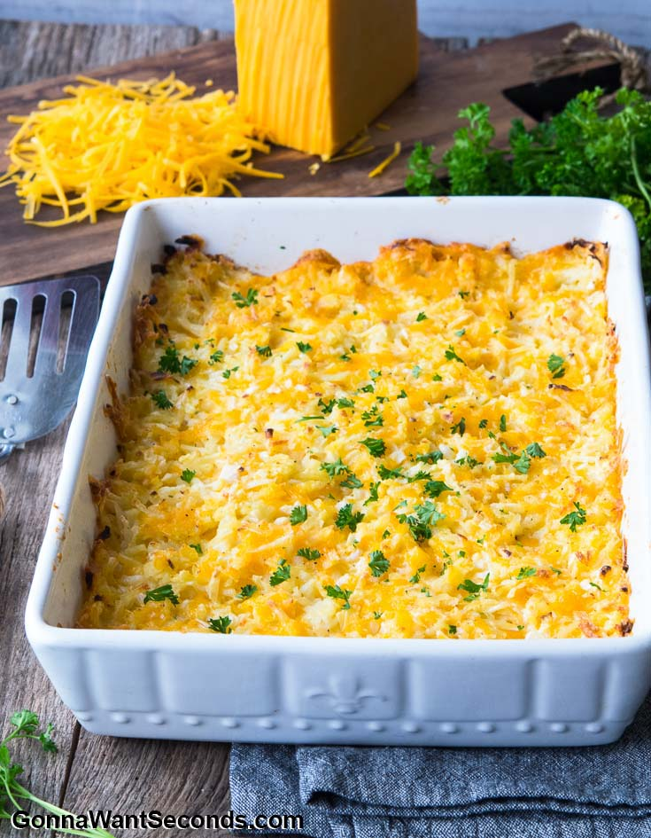 Hashbrown Casserole in a white baking dish, with shredded cheese at the side