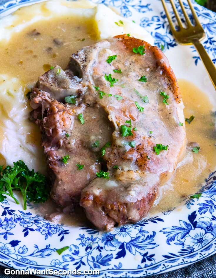 Instant pot pork chops and mashed potatoes, smothered with gravy, on a plate with fork
