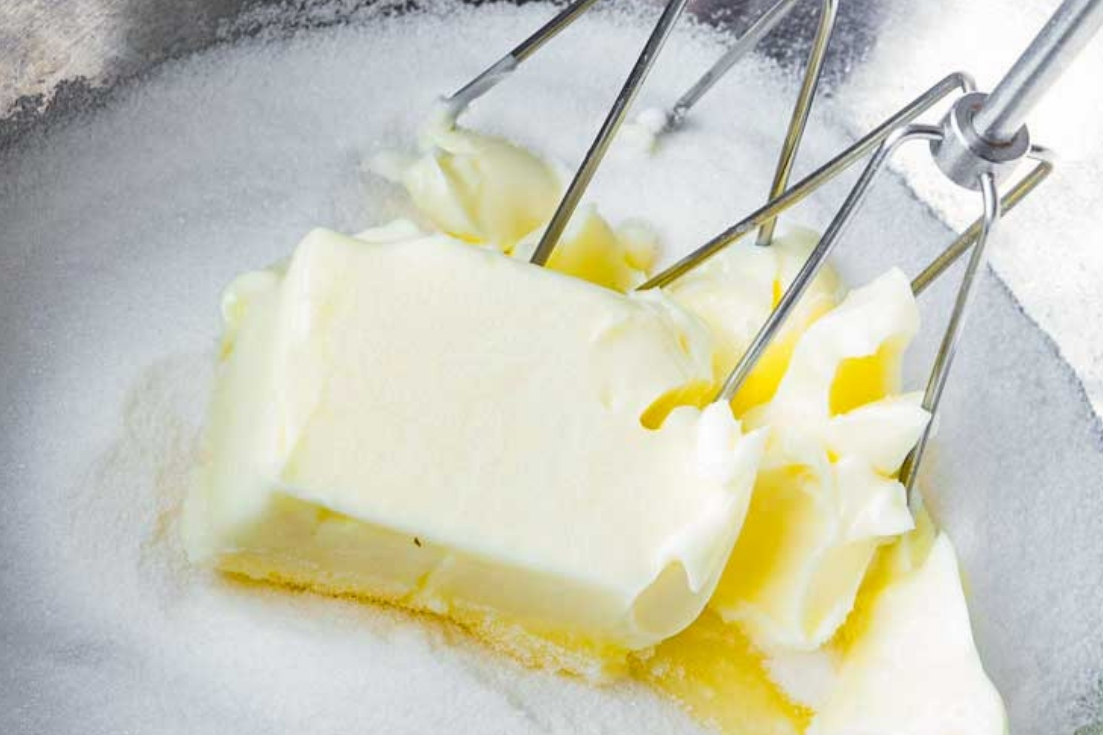 Mixing butter and sugar using electric mixer