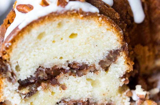 Sour cream coffee cake with glaze on top, garnished with chopped pecans