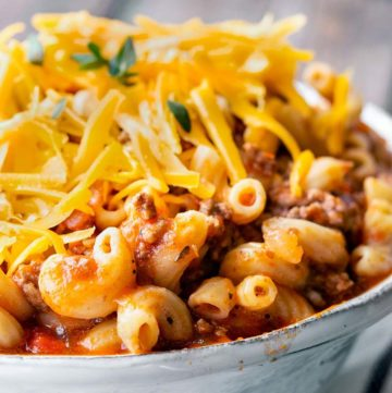 Crockpot Goulash in a bowl, topped with shredded cheese