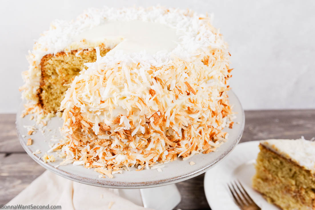 coconut cake with cream cheese frosting on a cake stand