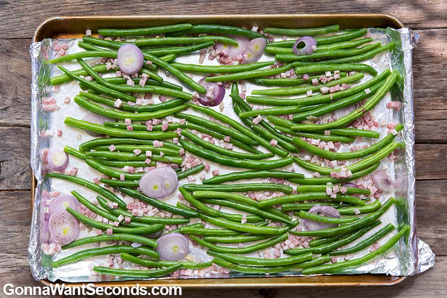 Roasted Green Beans arranged on an aluminum foil covered baking sheet