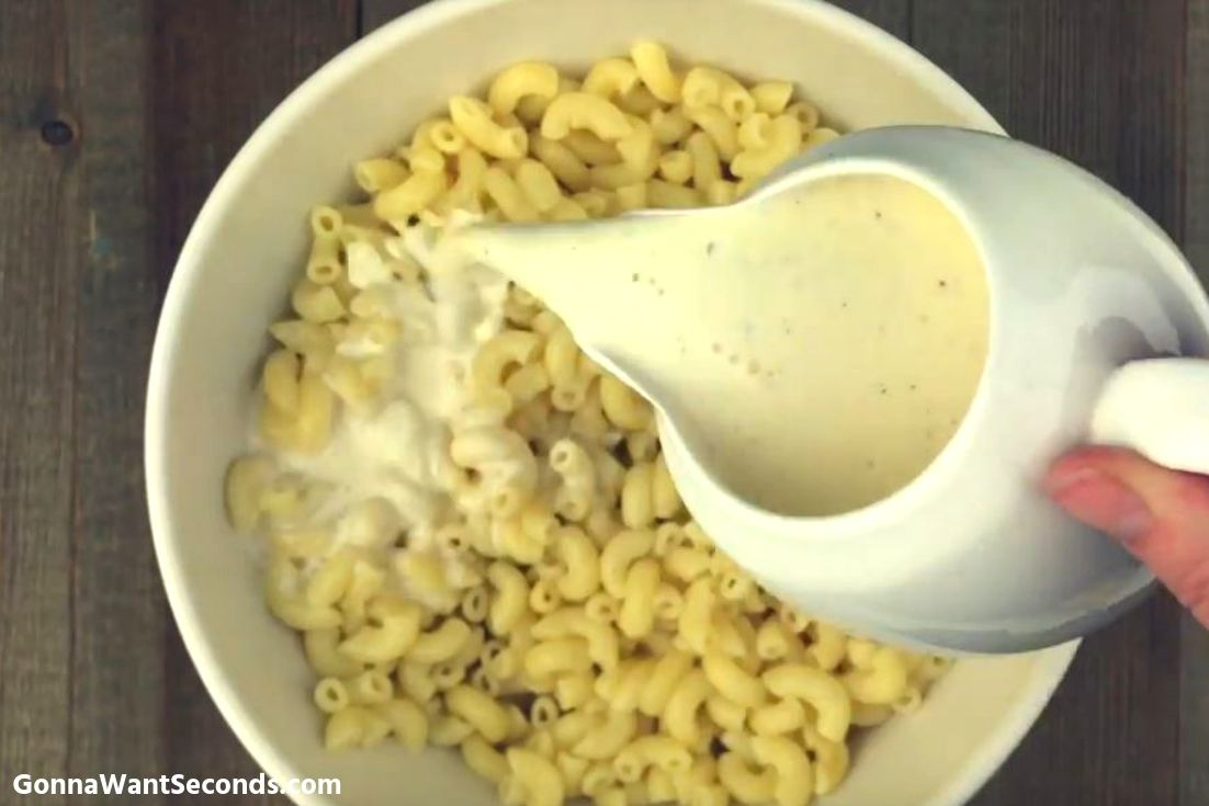 Pouring the dressing over cooked elbow macaroni for Hawaiian Macaroni Salad
