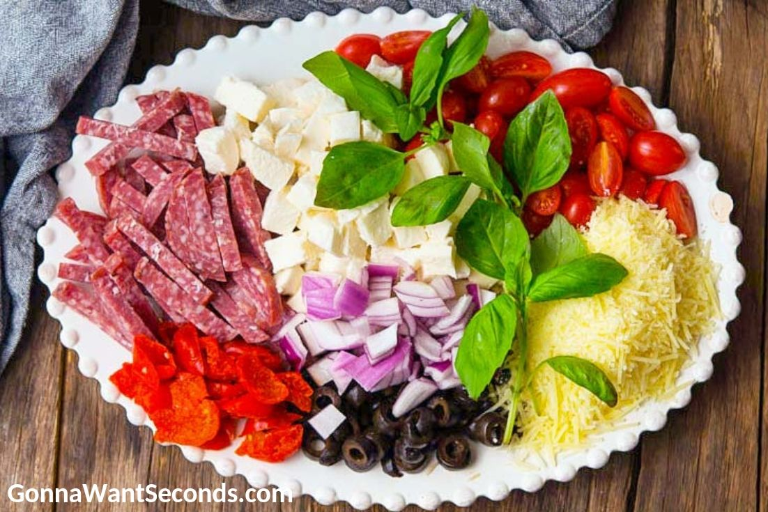 Chopped ingredients for Italian Pasta Salad on a large oval plate