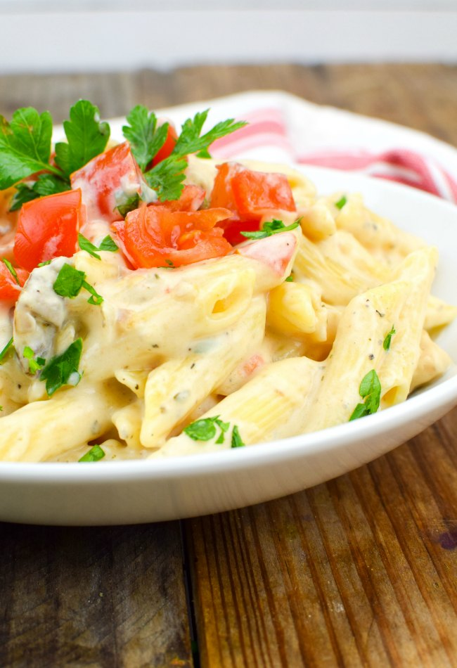 Chicken Alfredo topped with chopped tomatoes and parsley on a white plate