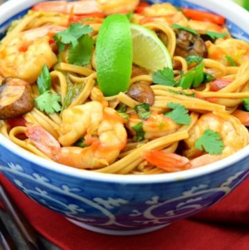 Shrimp Lo Mein topped with sliced limes, in a blue porcelain bowl