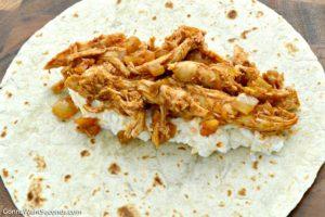 Cheesy chicken enchiladas filling in a flour tortilla