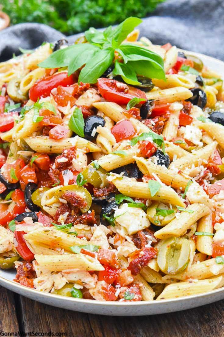 Mediterranean Pasta Salad on a plate, garnished with fresh basil