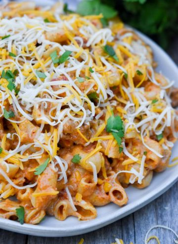 taco pasta topped with shredded cheese on a plate