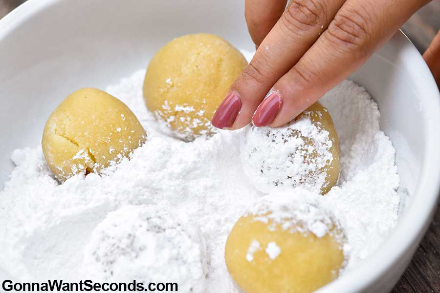 Rolling amaretti cookies in the confectioner's sugar