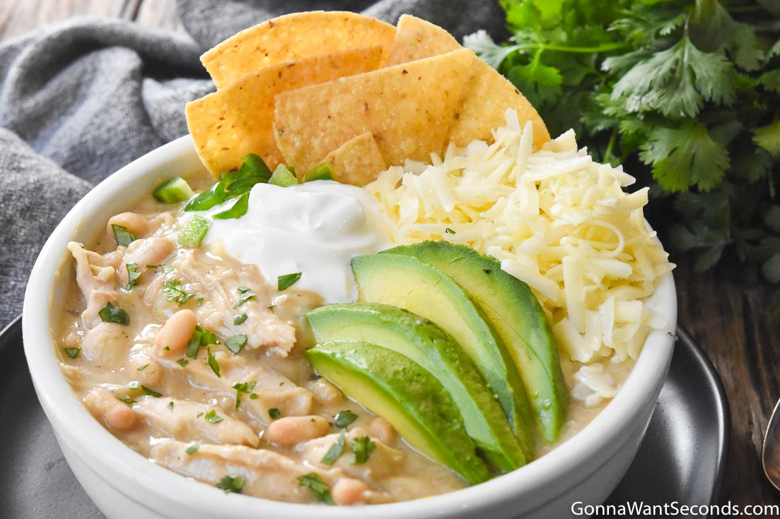 crockpot white chicken chili topped with sliced avocados, cheese, and tortilla chips, in a white bowl