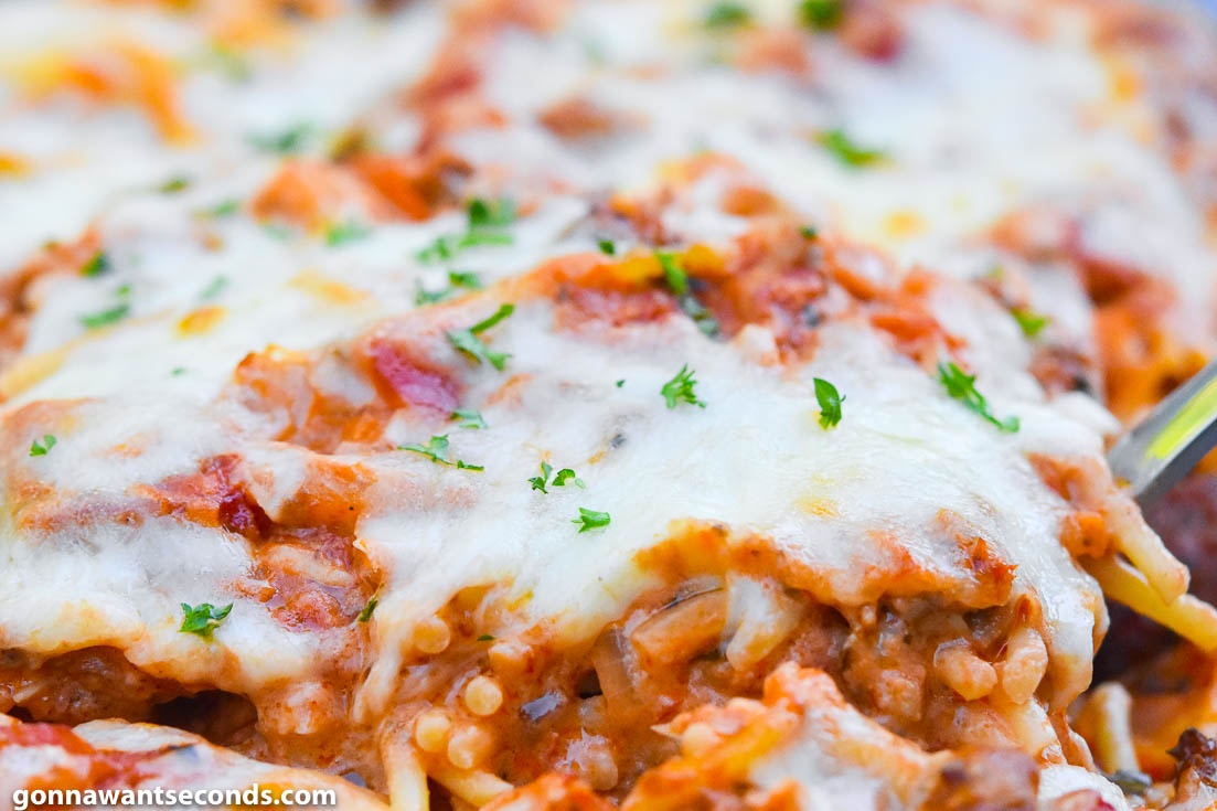 Scooping baked spaghetti from a casserole dish