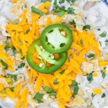 Creamy white chicken chili on a blue bowl, topped with jalapeno and cheese