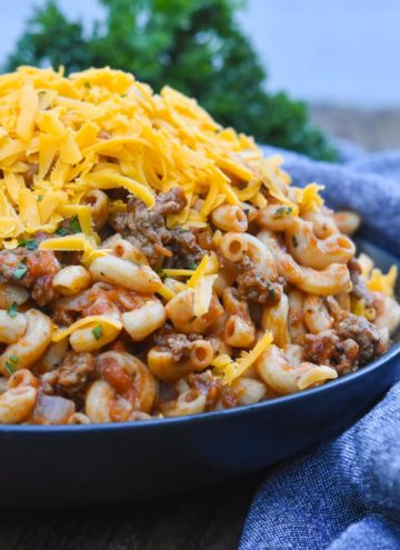 A bowl full of Hamburger Goulash, topped with shredded cheese