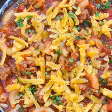 Instant pot goulash topped with shredded cheese in a blue bowl