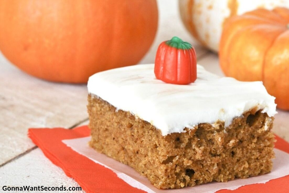 A slice of Pumpkin Bars with Cream Cheese Frosting with pumpkins at the back