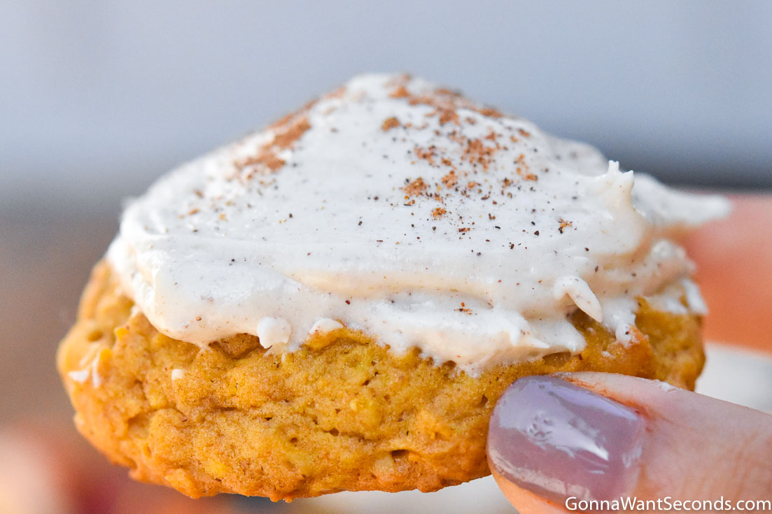 Holding Pumpkin oatmeal cookies with cream cheese frosting
