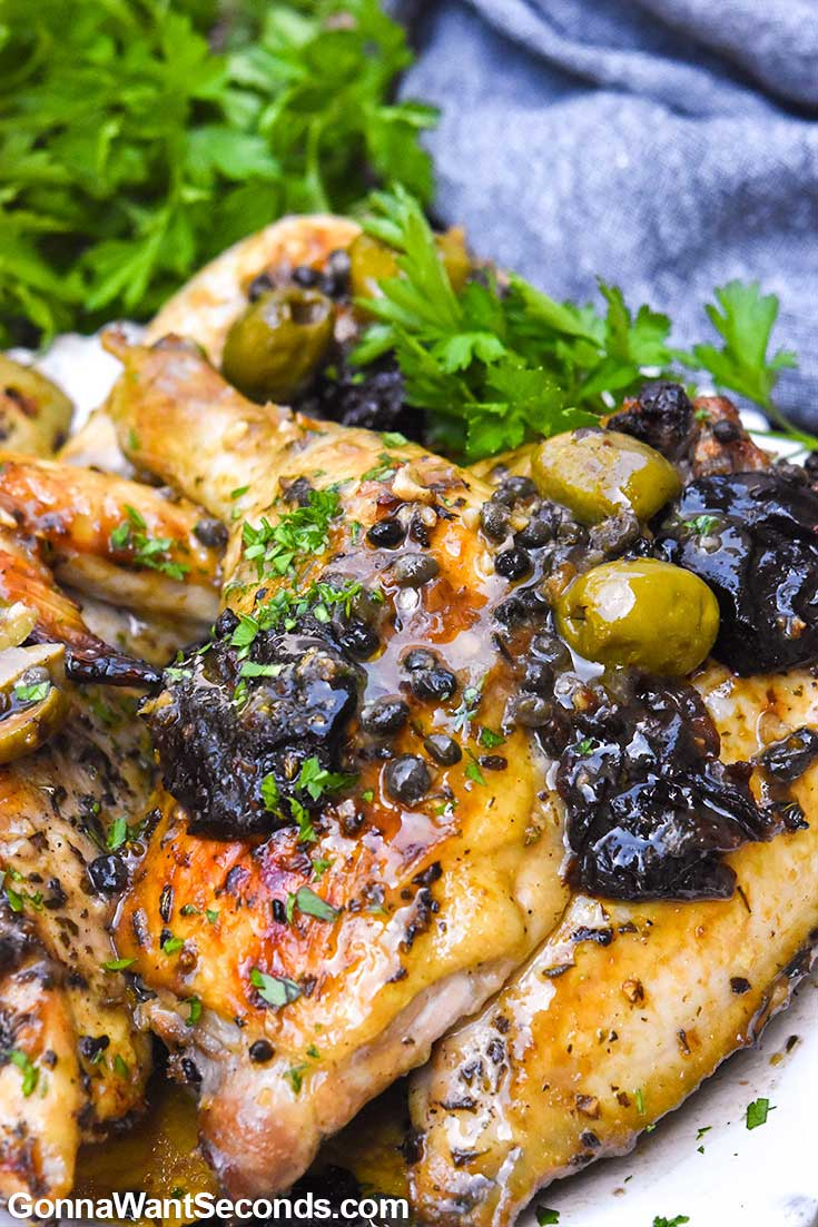 Chicken Marbella topped with capers and prunes, on a plate